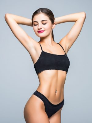 slim-body-of-young-woman-in-black-bikini-girl-with-healthy-sporty-figure-on-white-wall